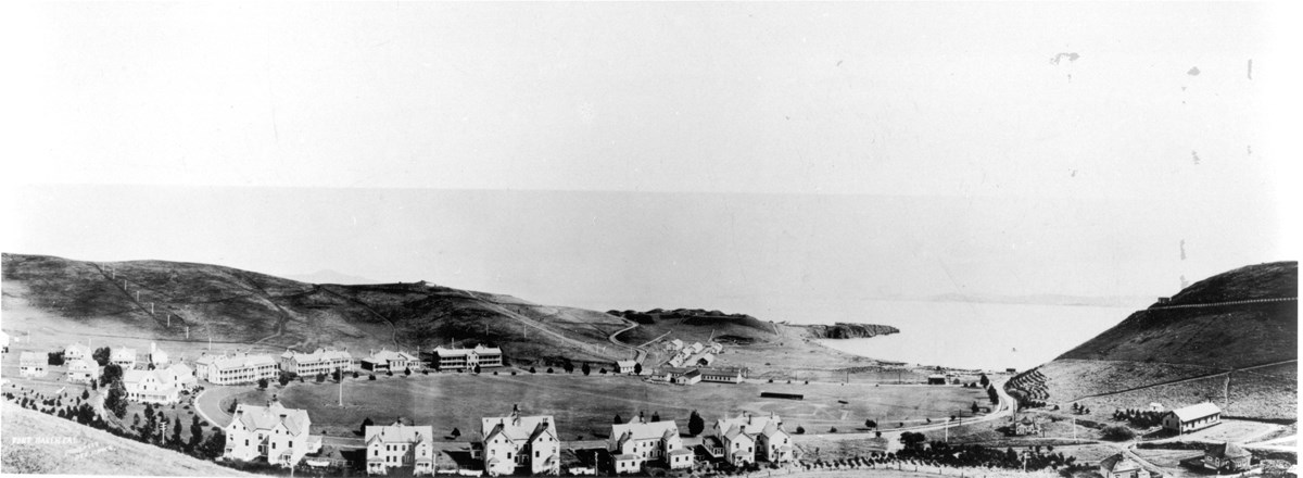 small historic buildings clustered around open landscape with ocean in the background