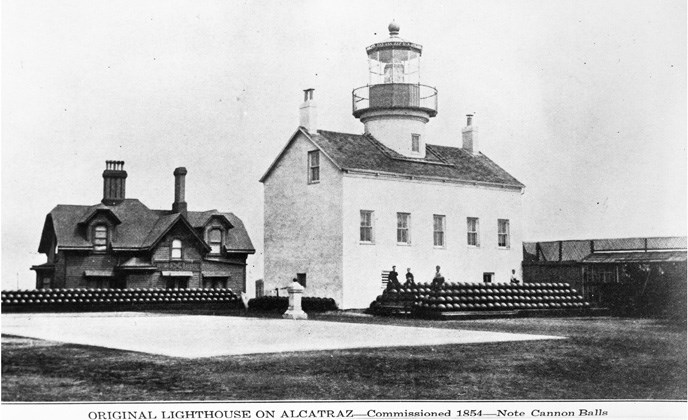 historic photo of white lighthouse with brick building in background