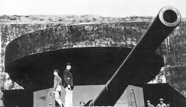 soldiers standing in front of large gun