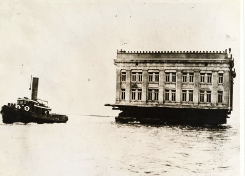 a tug boat pulling a building floating on a barge