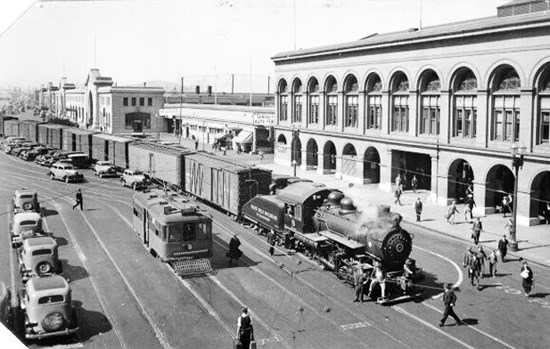 historic image of steam train and traffic in front of SF Ferry Building