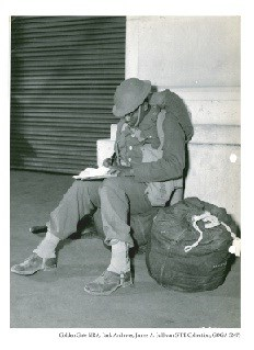 Private Joe Fleming, New York City, catching up on his book work as he awaits embarkation.