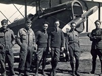 men in jumpsuits standing in front of biplane