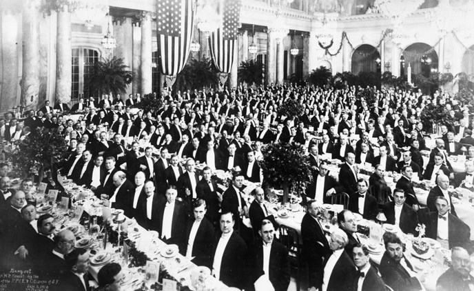 large group of formally dressed men in banquet hall