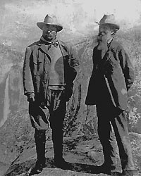 two men wearing hats standing at top of mountain
