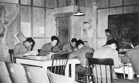 historic photo of Nisei soldiers sitting and studying at tables inside a historic building