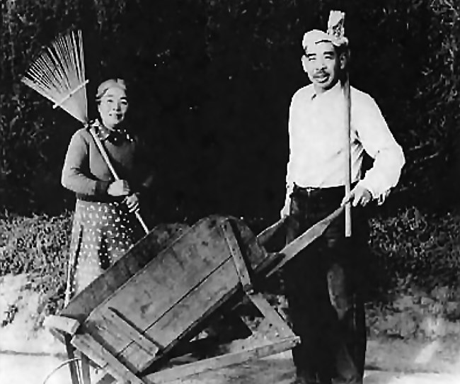 man holds barrel and woman holds rack in front of bush