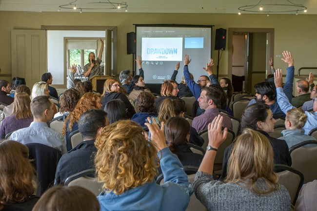 A crowd raises their hands as a ranger presents on sustainability in GOGA.