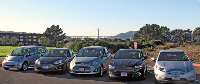 Five electric vehicles lined up at Fort Mason, with the Golden Gate Bridge in the background.