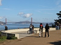 Visitors stand at a lookout at Lands End facing the Golden Gate Bridge which sits below a blue sky with clouds.