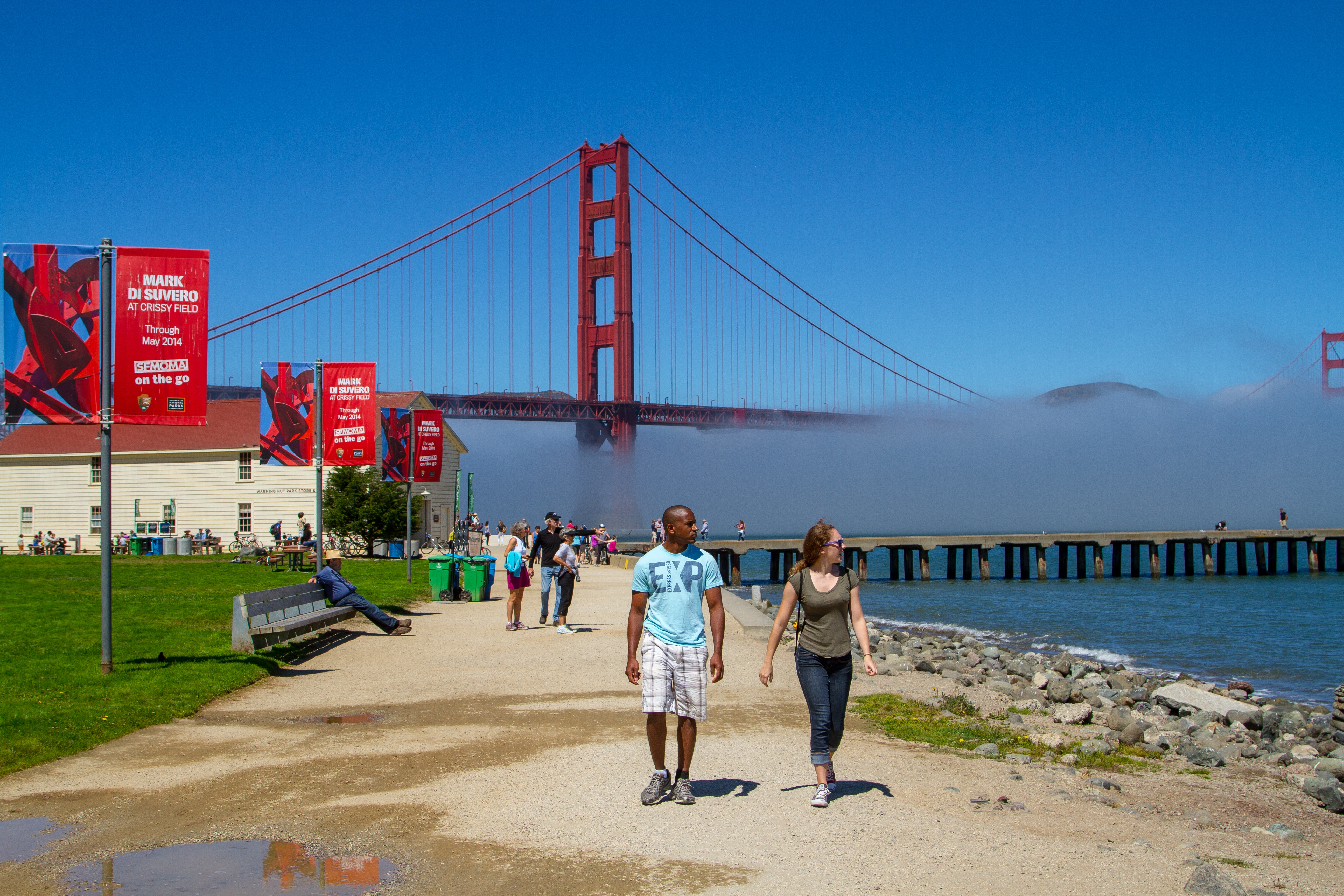 People walk along San Francisco Bay on a bright blue day with the Golden Gate Bridge and fog in the background. The white Warming Hut and red banners are left of the trail.