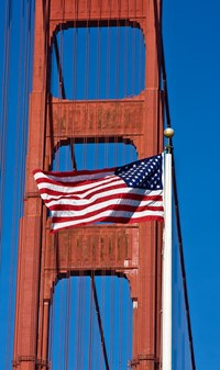 American flag at full staff with a tower and cables of the Golden Gate Bridge in the background.