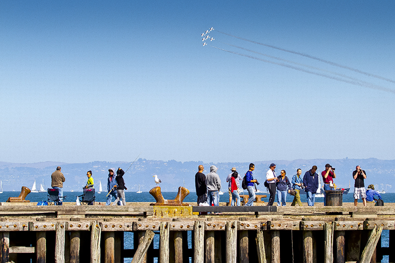 people on a pier during an air show