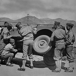 military men replace a tire