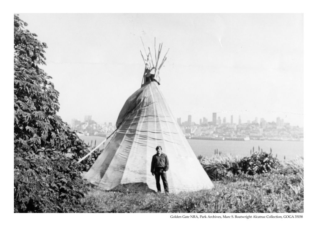 GOGA 35158-117 Marc S. Boatwright in front of a teepee constructed on Alcatraz.  San Francisco's skyline is visible in the back.