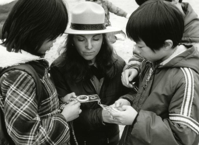 A ranger shows children how to orient a compass in the Marin Headlands.