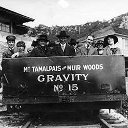 "People sit in metal car on track entitled ""Mt. Tam and Muir Woods Gravity No.15"""