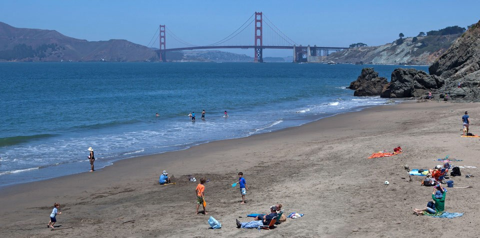 People playing and lounging on China Beach on a sunny day with Golden Gate Bridge behind