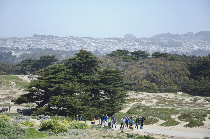 Hikers at Fort Funston with the San Francisco skyline in the background