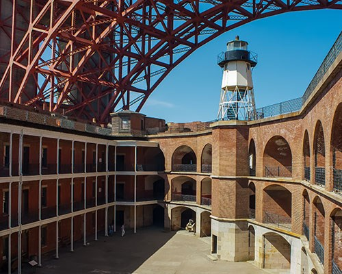 Fort Point and its Lighthouse in view on a sunny day as visitors roam around.