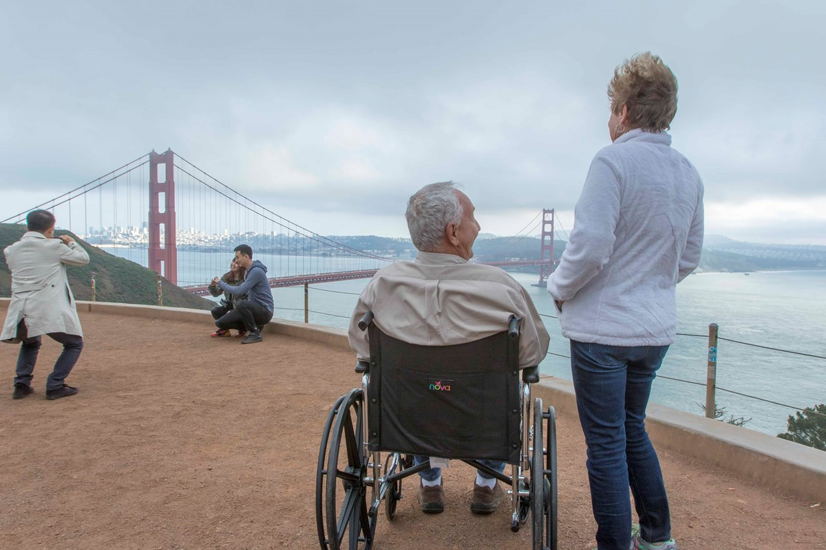 Man in a wheelchair besides a standing women overlooking an orange bridge