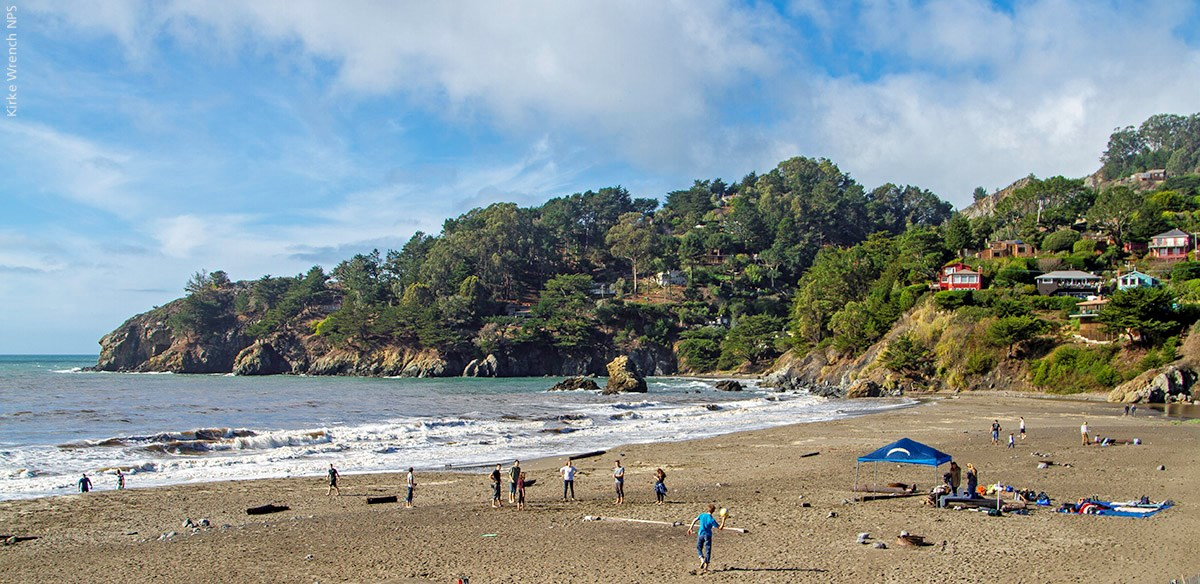 People playing on Muir Beach with the ocean and wooded hills in the background