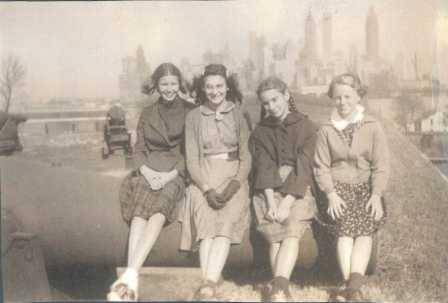 Betty Nickerson and friends sit on a cannon atop Fort Jay with NYC in the background.