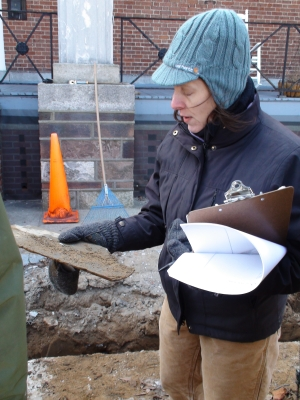 Archaeological Consultant Linda Stone supervised the recent sidewalk construction in the historically sensitive quadrangle in Fort Jay.  Here she observes a piece of slate, probably once used to shingle the roofs in the fort, which was excavated from a fill layer several feet down.