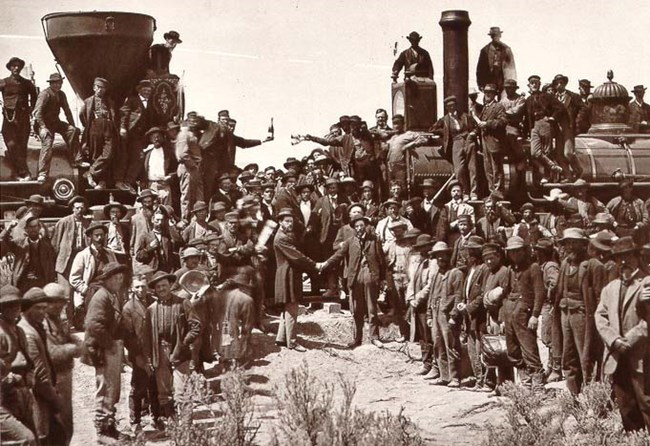 Men stand beside two locomotives celebrating the completion of the first transcontinental railroad.