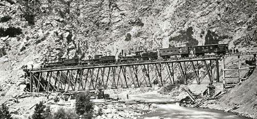 Picture of Transcontinental Railroad Bridge with train constructed in the Wasatch Mountains of Utah. Photograph by Andrew J. Russell, 1869