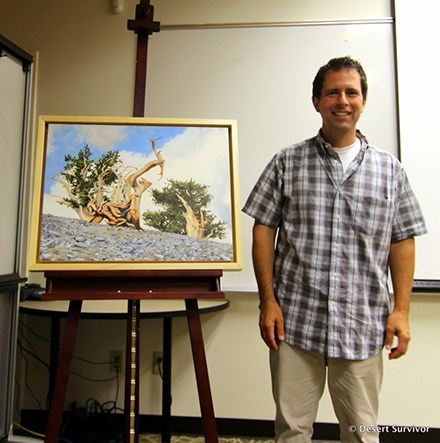 Man standing next to detailed painting of bristlecone pines