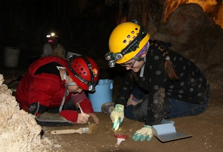 Kids cleaning cave floor