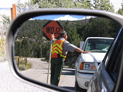 Maintenance worker holds back traffic for construction