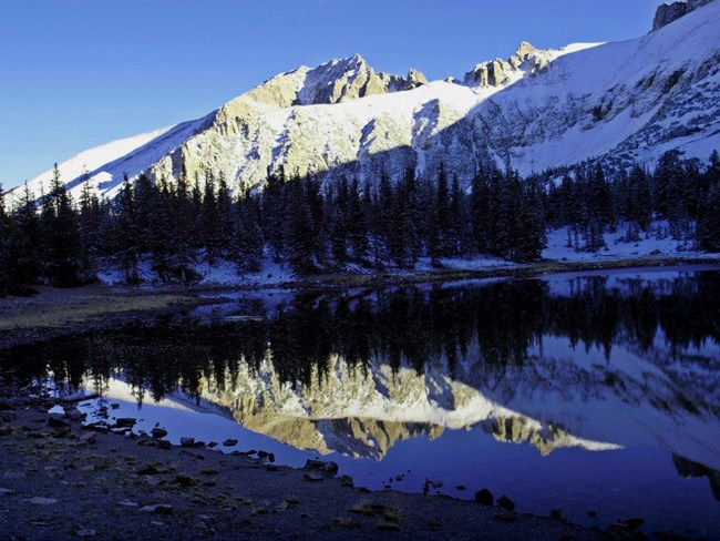 A glassy smooth lake with rugged mountains dusted in snow.
