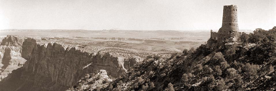 Sepia toned image of Desert View Watchtower on the far right, looking out over Grand Canyon cliffs beyond.