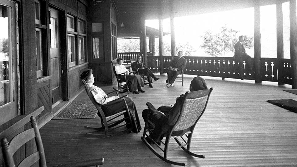 Black and white historic photo of El Tovar Hotel front porch with several well dressed people reclining in rocking chairs