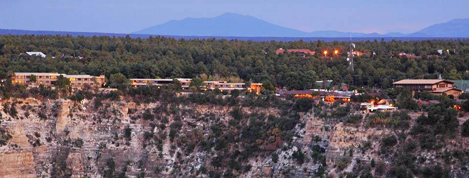 Overview of Grand Canyon Village as seen from a distance at twilight. Building lights are coming on.