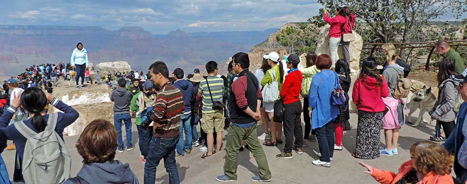 a crowd of people wearing a variety of colorful clothing, on an upper level of Mather Point scenic overlook.