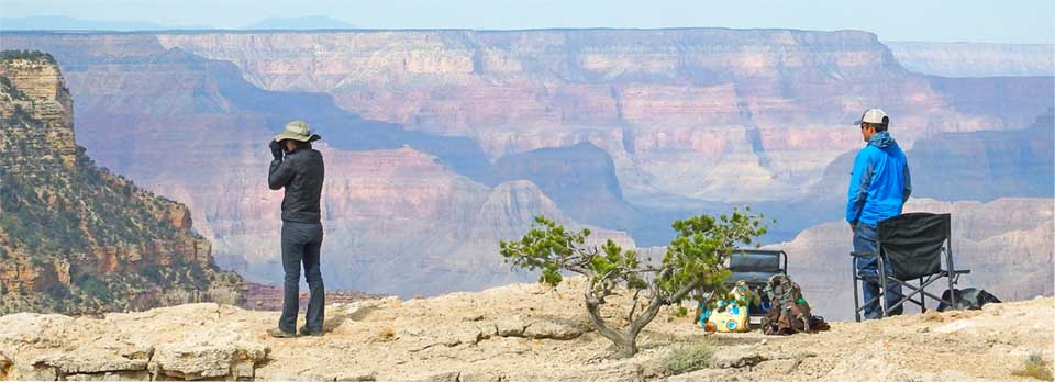 A man and a woman with binoculars standing on a rock ledge overlooking Grand Canyon. They are looking for raptors.