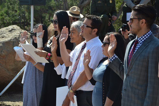 A close up shot of six people as they raise their right hand as they are sworn in as United States Citizens during a naturalization ceremony.