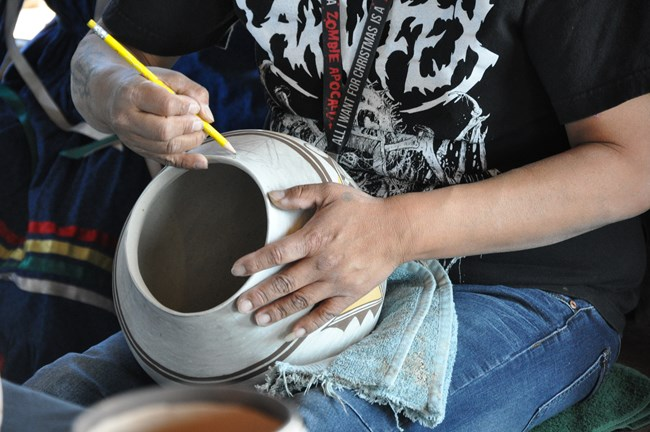 American Indian artist holds pale bowl in lap. One hand holds the bowl while the other hand traces designs and patterns onto the bowl.