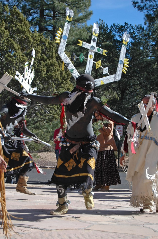 Dishchii' Bikoh' Apache Group from Cibecue, Arizona, demonstrates the Apache Crown Dance. He is wearing a three pronged head piece that is white with yellow, blue, green, and black embellishments. His head is completely covered with cloth while his upper