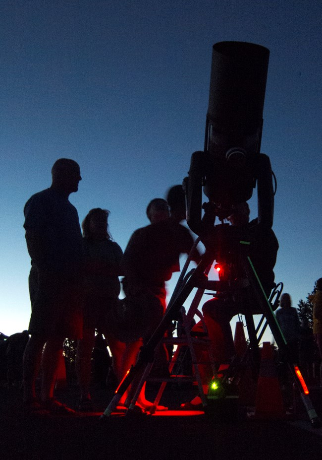 Red lights illuminate a large telescope. People gather around the telescope, trying to look through.