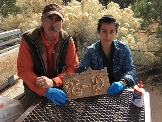 "Becca and Ted hold trash art they constructed out of littered cigarette butts found at and around the Grand Canyon Visitor Center. The art reads, ""How long does it take for a cigarette filter to decompose? 18 months - 10 years."" November 2017."