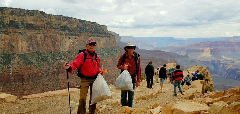 Volunteers holding trash bags standing along a trail near the rim of Grand Canyon.