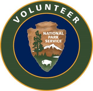 "National Park Service Volunteer patch is circular with the words ""volunteer"" in white letters against a green outer circle. An inner circle is navy blue and has an NPS arrowhead graphic with a bison, a tall tree, and a snow-covered mountain positioned wit"