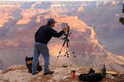 Landscape painter at work at his easel with sunrise on the Grand Canyon walls in the background.
