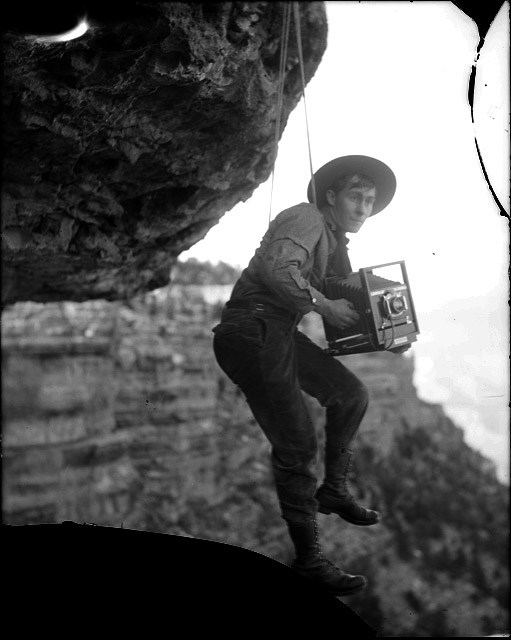 A man hangs down on a rope between two boulders holding a large, antique camera.