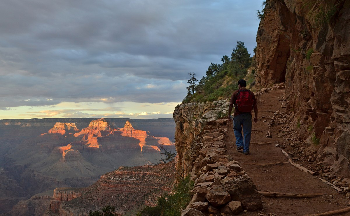 A single man with a backpack hikes uphill, towards a golden sunset background.