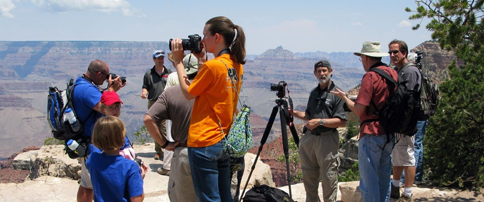 A group of photographers with tripods mingle on a scenic overlook.